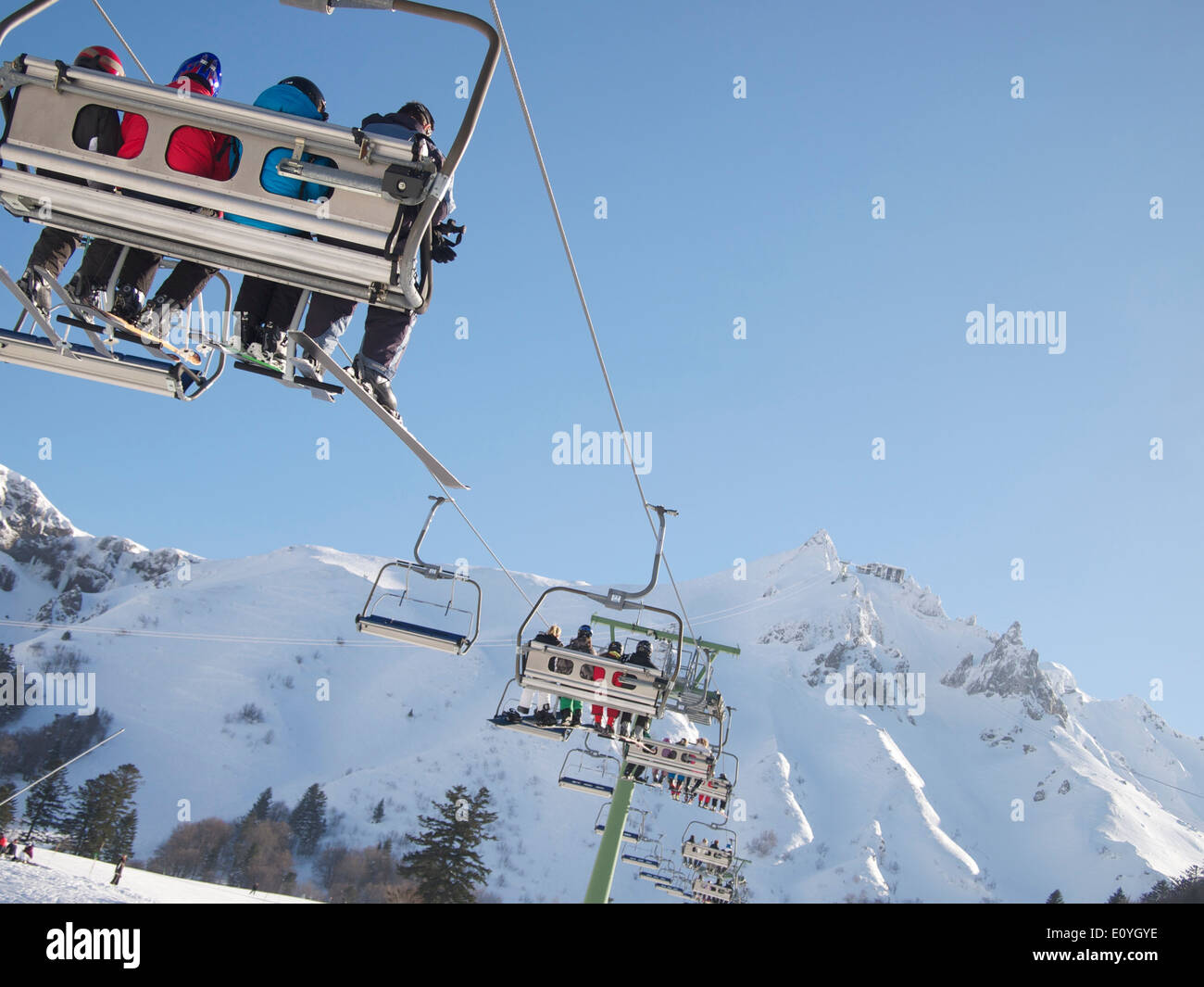 Skiers on a ski lift at Le Mont-Dore ski resort, Massif of Sancy, Auvergne, France - Stock Image
