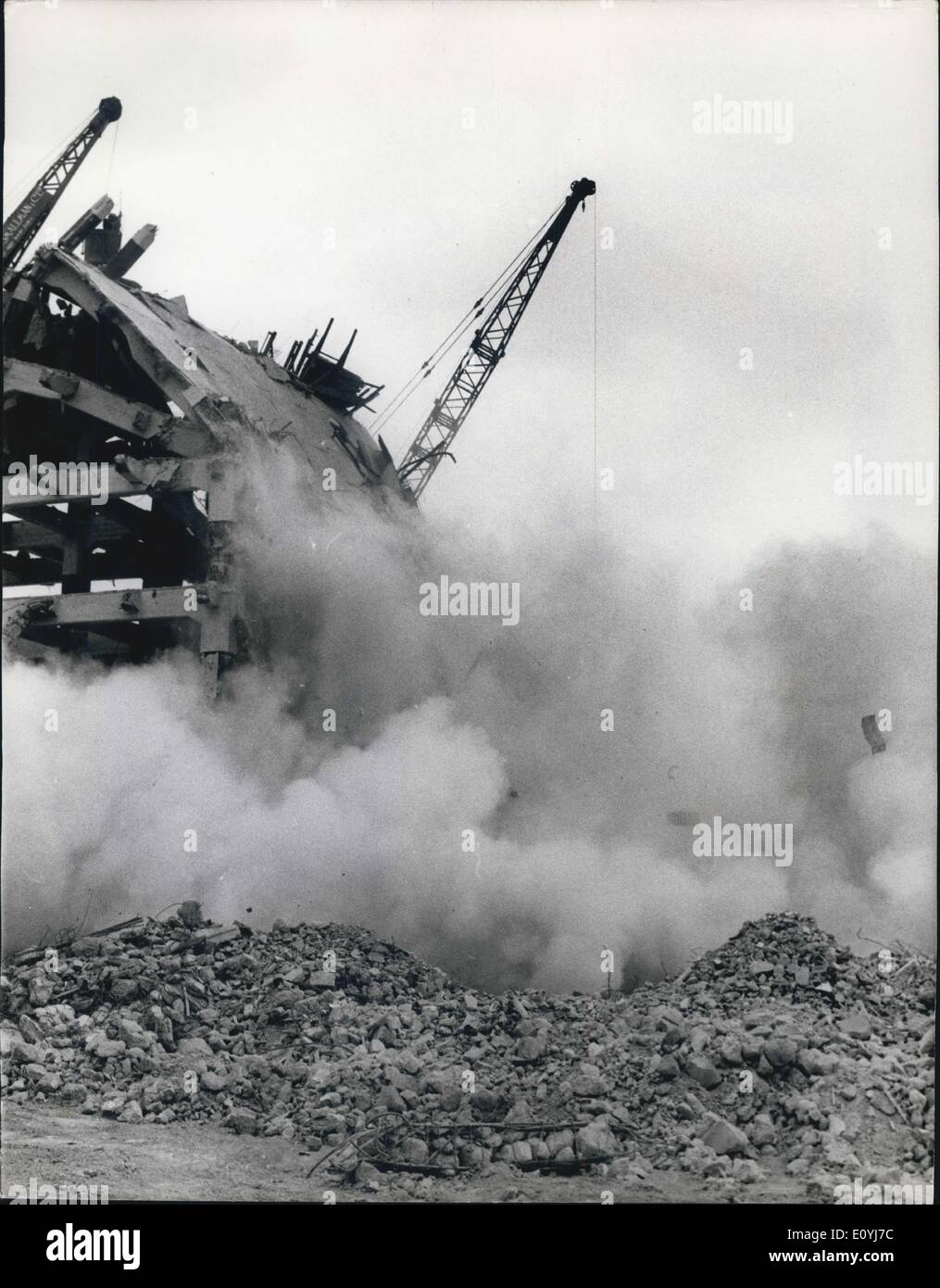 Jul. 06, 1970 - Tower Succumbs to Persuasion. Hours of hammering with two one-ton steel balls swung, pendulum-like from a crane, failed yesterday to knock down the last of three 120ft high, 250-ton towers of a 300ft long granary at Nine Elms. The 36-year old building was being demolished to make way for the new market to replace Covent Garden. A workman inside a crane bucket had to cut six steel rods with an oxy-acetylene torch before the upper section of the last fragment of a local landmark on the south bank of the Thames collapsed in a cloud of dust - Stock Image