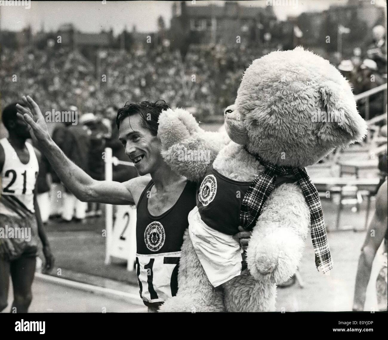 Jul. 07, 1970 - The Commonwealth game in Edinburgh Scotland's Lachie Stewart and his Mascot: Photo shows Lachie Stewart. of Scotland, hold a giant teddy bear, his team's mascot, and waves to the crowd after he had won the 10,000-metre race yesterday, beating Australia's Ron Clarke, who finished second. - Stock Image
