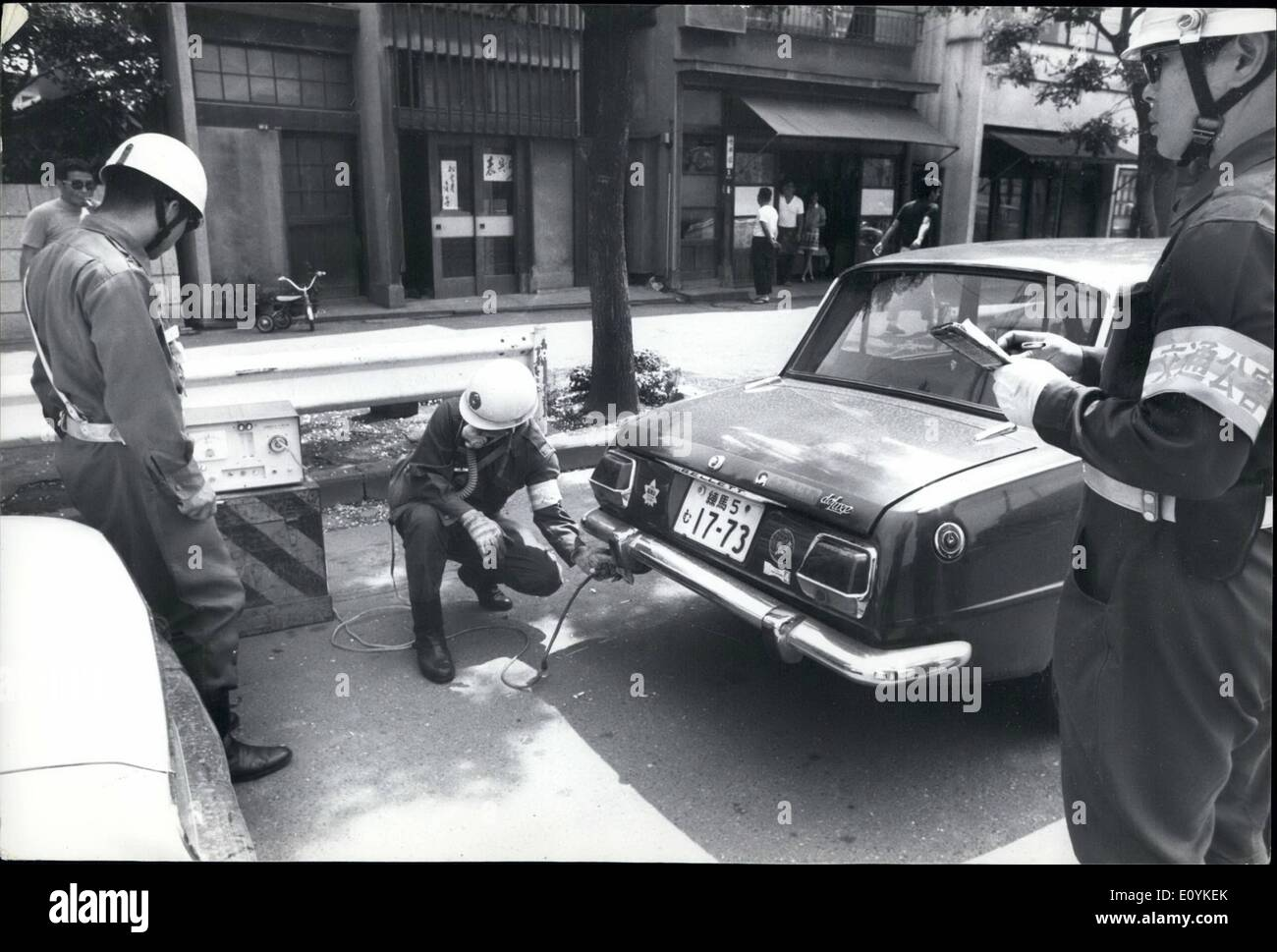 Aug. 08, 1970 - Tokyo Police Check Car Exhausts: Tokyo traffic policemen wearing gets masks are carrying out daily check of automobile exhausts in an attempt to control air pollution. On their first check with measuring instruments plugged into the exhaust pipes and coupled to gauges, 40 percent emitted exhaust gas with higher CO levels than the legal limit of 5.5 per cent, when the engine is idling. Owners of cars that issued high levels of CO were ordered to tune up their engines immediately, - Stock Image
