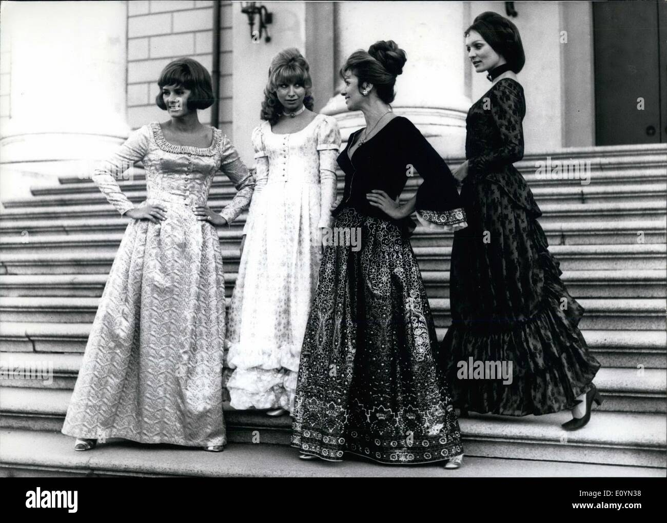 Nov. 11, 1970 - Show of Bavarian costumes in Munich: In front of the Bavarian opera the photographer met these four young ladies. All models coming from Munich (Germany), present the latest fashion of a special shop for Bavarian and traditional costumes. Photo shows from left to right: Dora wears a long evening ''Dirndl'' (Bavarian National Costume) made a raspberry red brocade called ''Dorothee'' Conny wears a long blue Dirndl made of wool which ca be washed trimmed with beige lace; It is called ''Cristallina'' - Stock Image