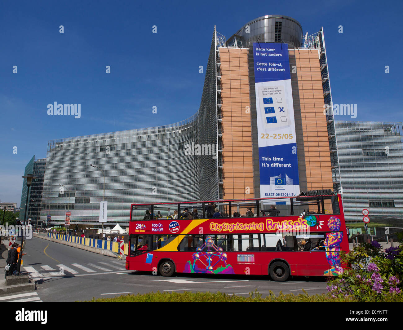Citytrip sightseeing hop on hop off tourism bus at the Berlaymont building in the EU district of Brussels, Belgium - Stock Image