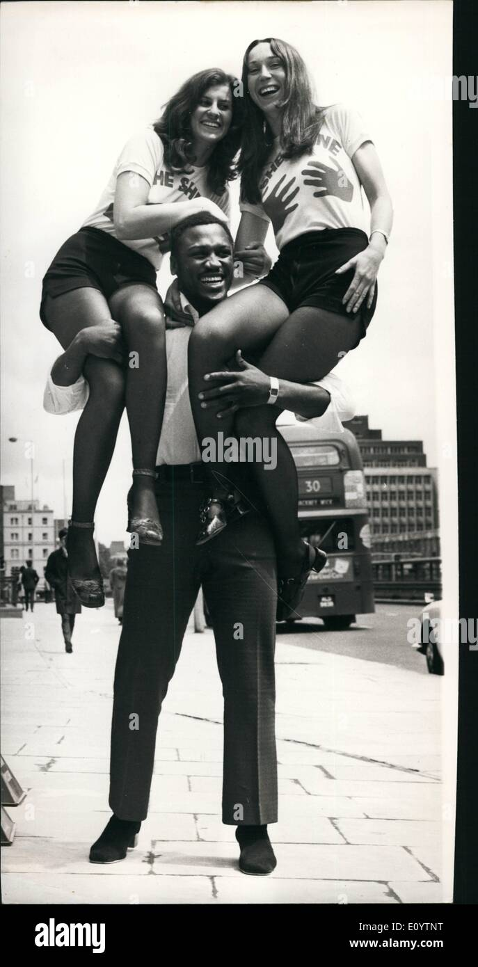 Jun. 06, 1971 - Joe Frazier At TV Studios: World heavyweight boxing champion Joe Frazier who will appear in the Thames TV Programme 'Tea Break' which goes out on Thursday, was at the studios today with two of London's only shoeshine girls, Pavla Podhrazska and Jane Green ,who also appear in the programme. Photo Shows Joe Frazier holds up Pavla Podhrazska (left) and Jane Green, at the TV Studios today. - Stock Image
