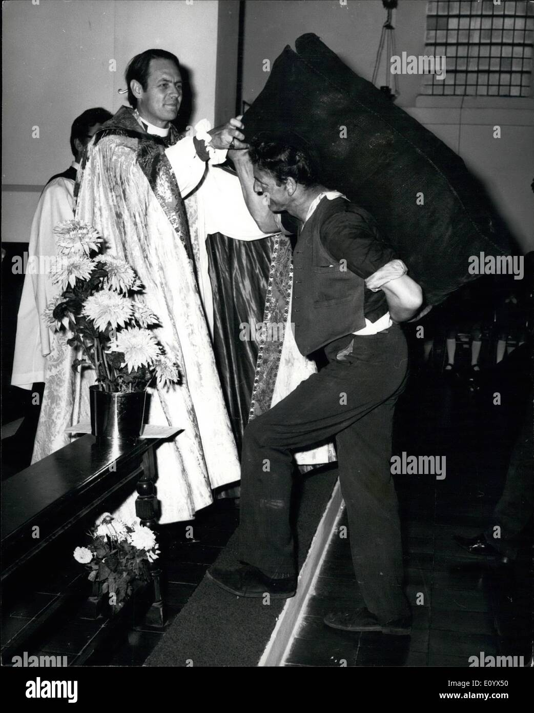 Sep. 09, 1971 - Workers' Thanksgiving Service: Taking delivery of some best household nuts at the altar of St. Barnabas Church on the G.L.C.'s Downham council estate yesterday - the Rt. Rev. David Sheppard, Bishop Suffragan of Woolwich, accepting a gift from Mr. Lal Roff, 47, a local coalman, during a workers' thanksgiving service. The congregation included nurses, dustmen and cleaners who carried the tools of their trade. - Stock Image