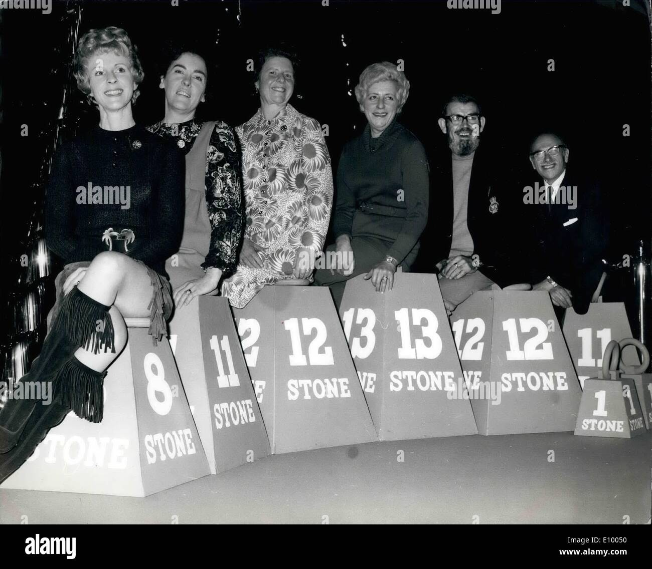 Jan. 01, 1972 - Happy weight-watchers: Six patients who appeared at the Albert Hall meeting to mark Weight-Watchers' fifth birtday, weighed 132 st. 11 lbs the start of their course and 63 st. 13 lbs at the end. they thus lost more than half their weight. Photo shows the six weight-watchers' sitting on ''Weights that show the number of stones each has shed. They are L-R: Mrs. Joyce Ashmore, Mrs Barbara O'Reilly, Mrs Betty Lary, Mrs Esta Napp, Mr George Eaton, and Mr. Charles Grilles - Stock Image