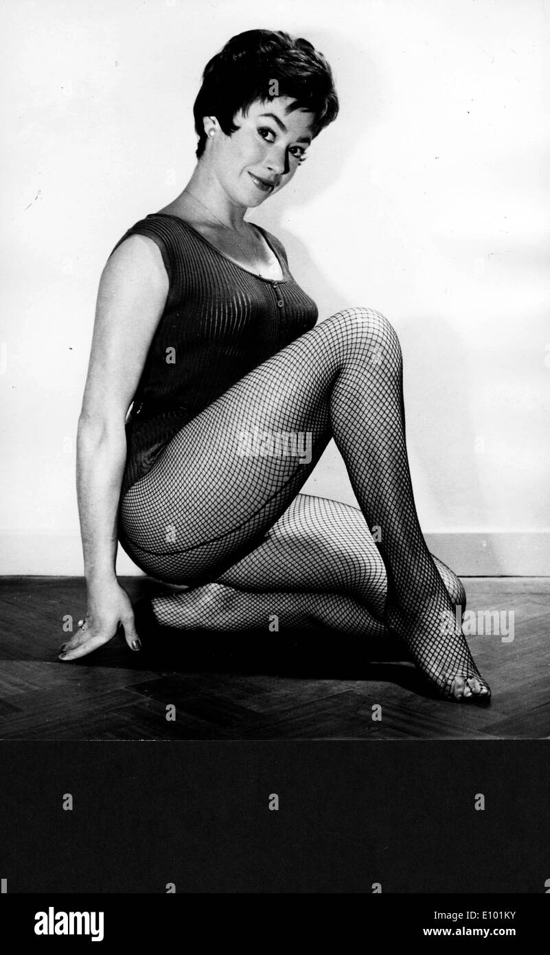 English Dancer actress GILLIAN VAUGHAN poses in fishnet stockings in a studio - Stock Image