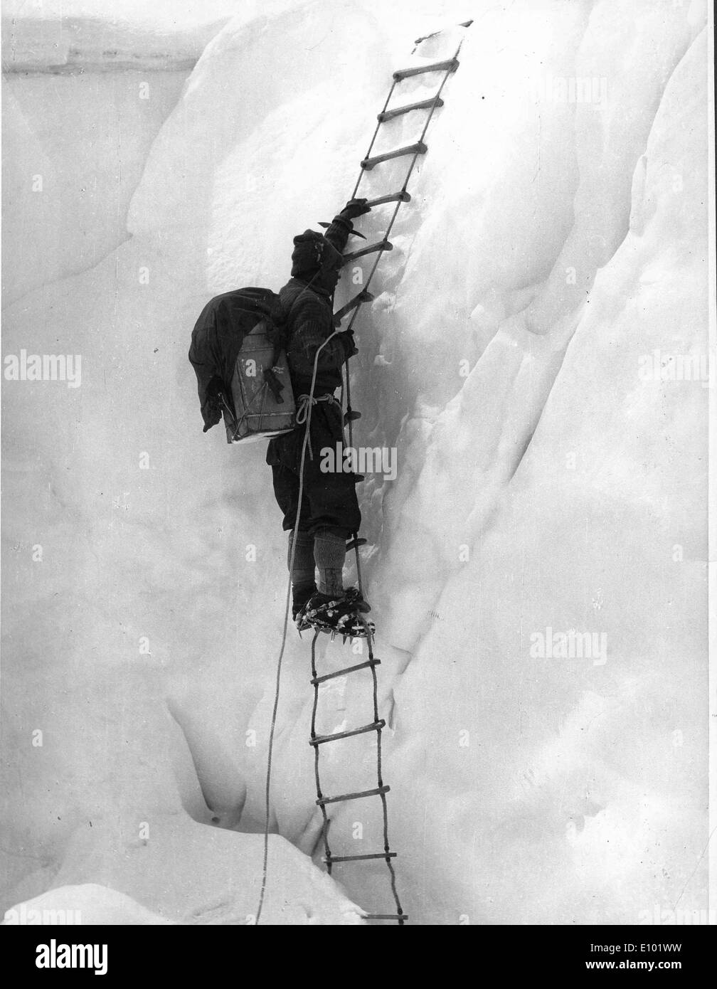 MOUNT EVEREST explorer climbing an icy side by ladder - Stock Image