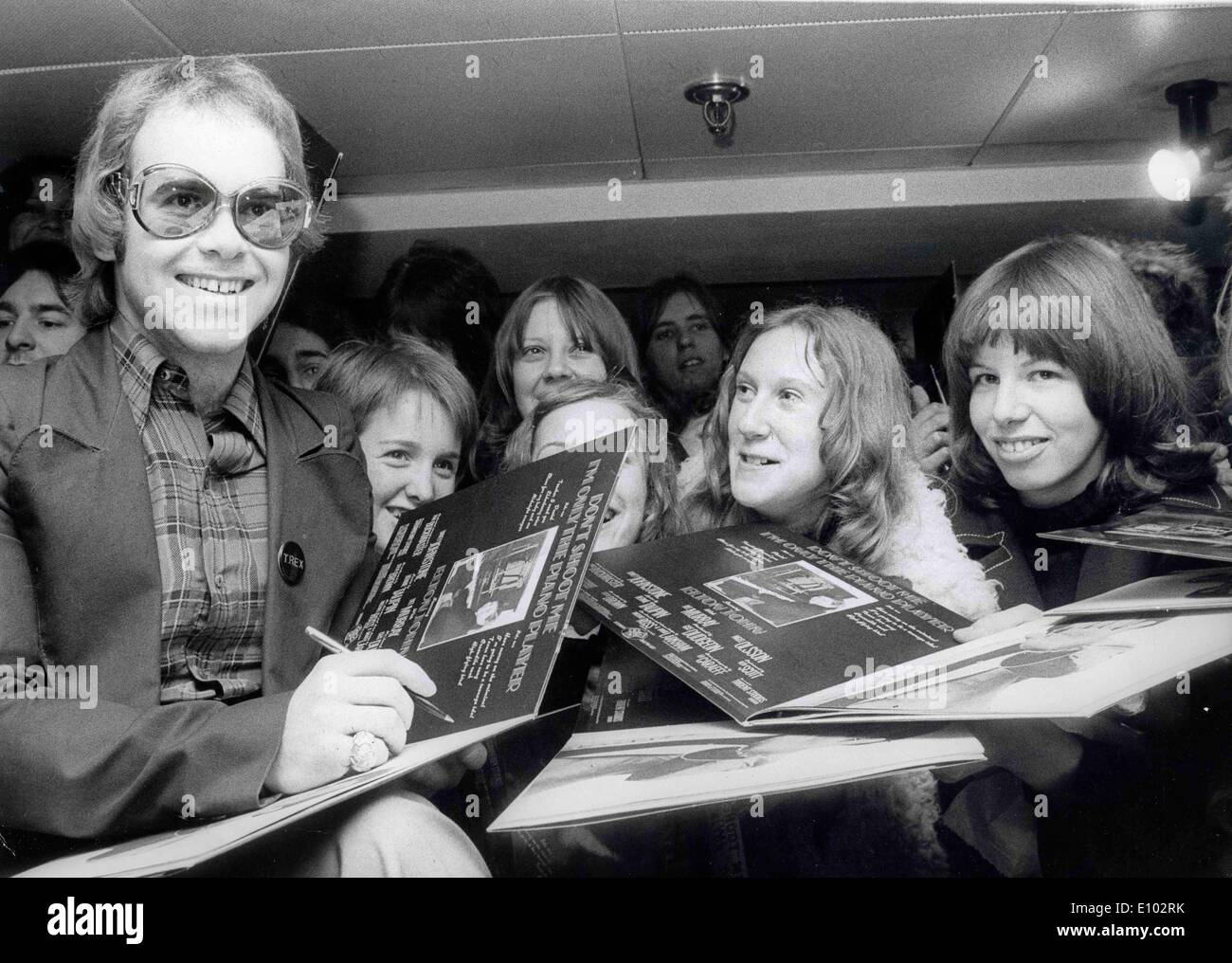 A young ELTON JOHN autographs albums for fans. - Stock Image