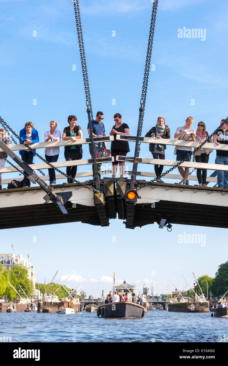 Amsterdam Magere Brug, Skinny Bridge, with people tourists visitors watching boats on the river Amstel. Seen from Stock Photo