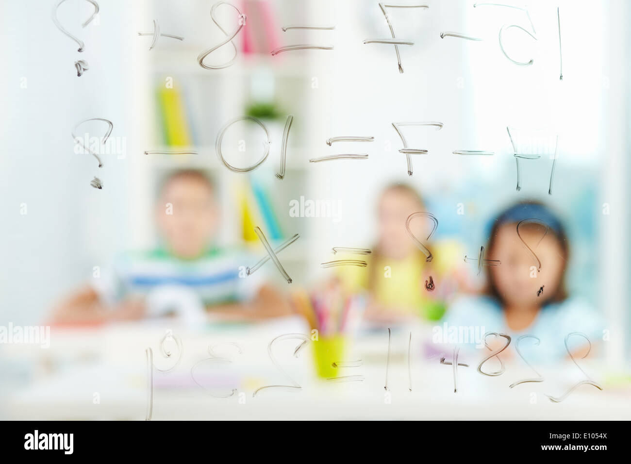 Image of sums written on transparent board with schoolmates on background - Stock Image