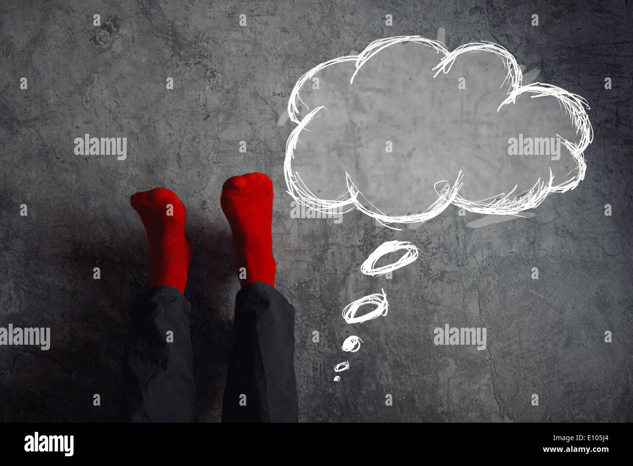 Legs up the wall, putting feet up with think balloon. Man wearing red socks in relaxing yoga pose with his legs on the wall. - Stock Image