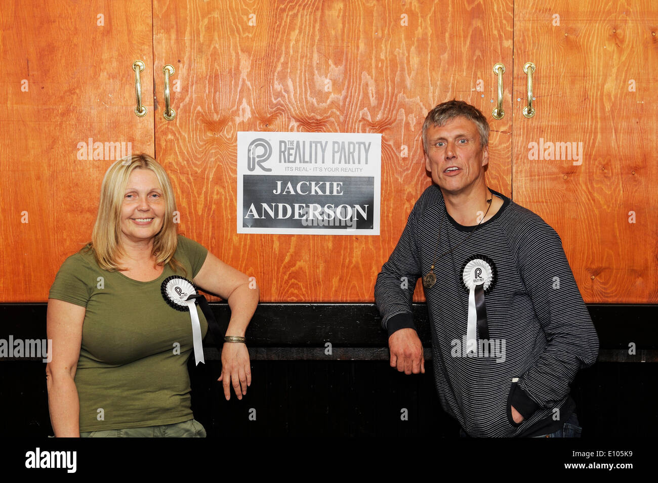 Irlam, Manchester, UK. 20th May 2014. Reality Party candidate Jackie Anderson stands beside her poster with Bez from the Happy Mondays at a campaign meeting to plan election stategy. Credit:  Dave Ellison/Alamy Live News - Stock Image
