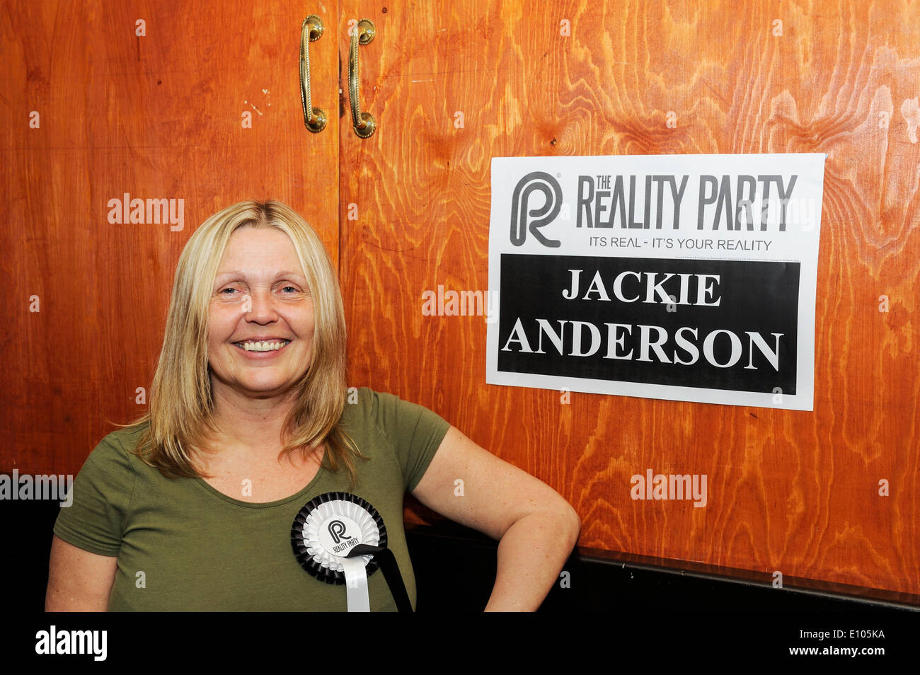 Irlam, Manchester, UK. 20th May 2014. Reality Party candidate, Jackie Anderson, stands beside one of her posters at a campaign meeting. Credit:  Dave Ellison/Alamy Live News - Stock Image