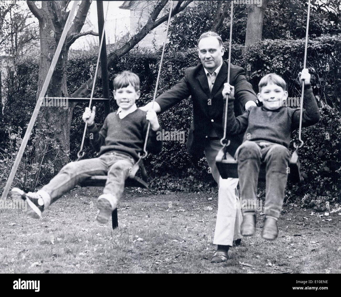 Aug 08, 1972 - Belfast, Northern Ireland, United Kingdom - WILLIAM CRAIG at home in the backyard pushing his two Stock Photo