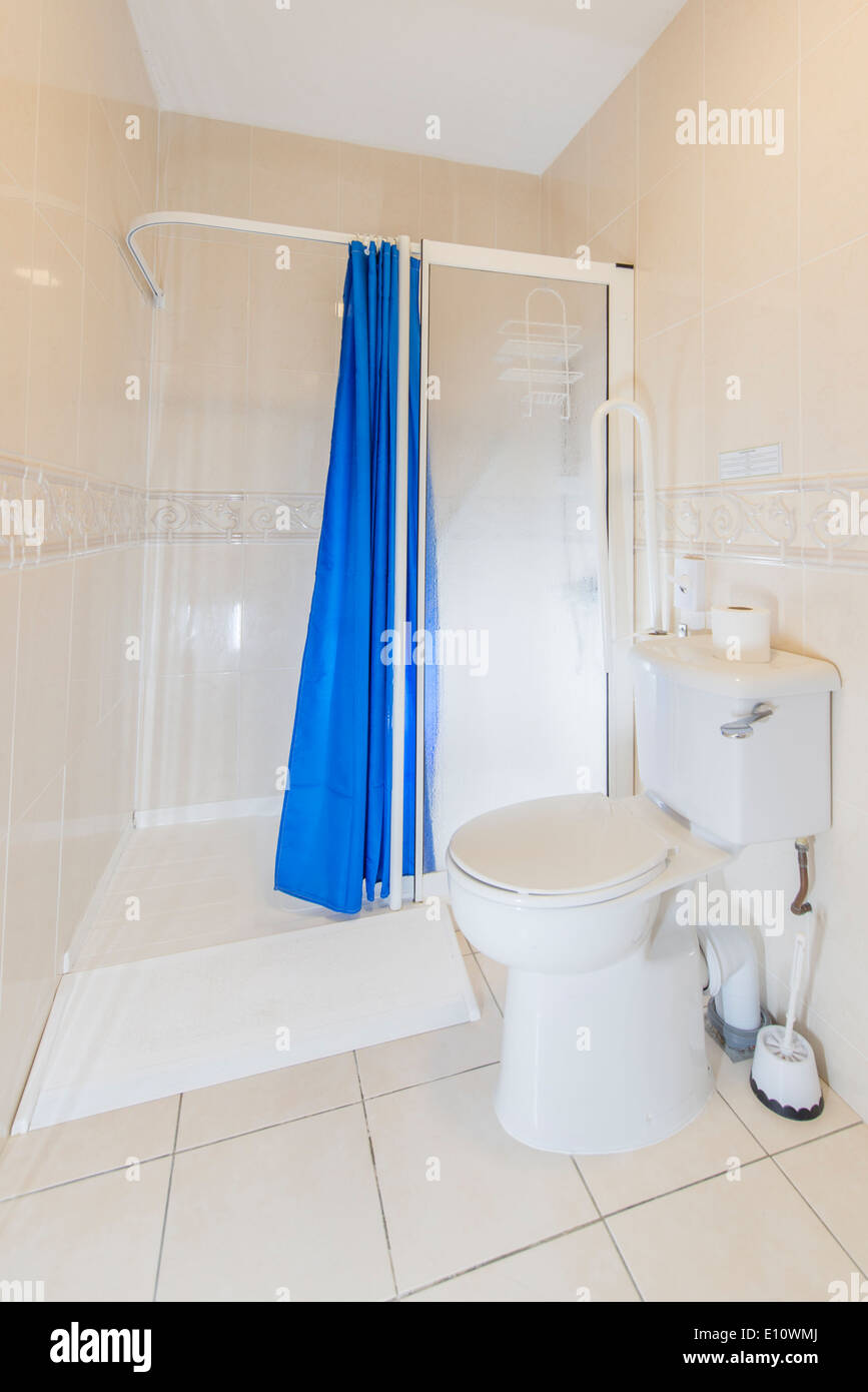 A disabled wheelchair access en-suite toilet and shower in a hotel ...