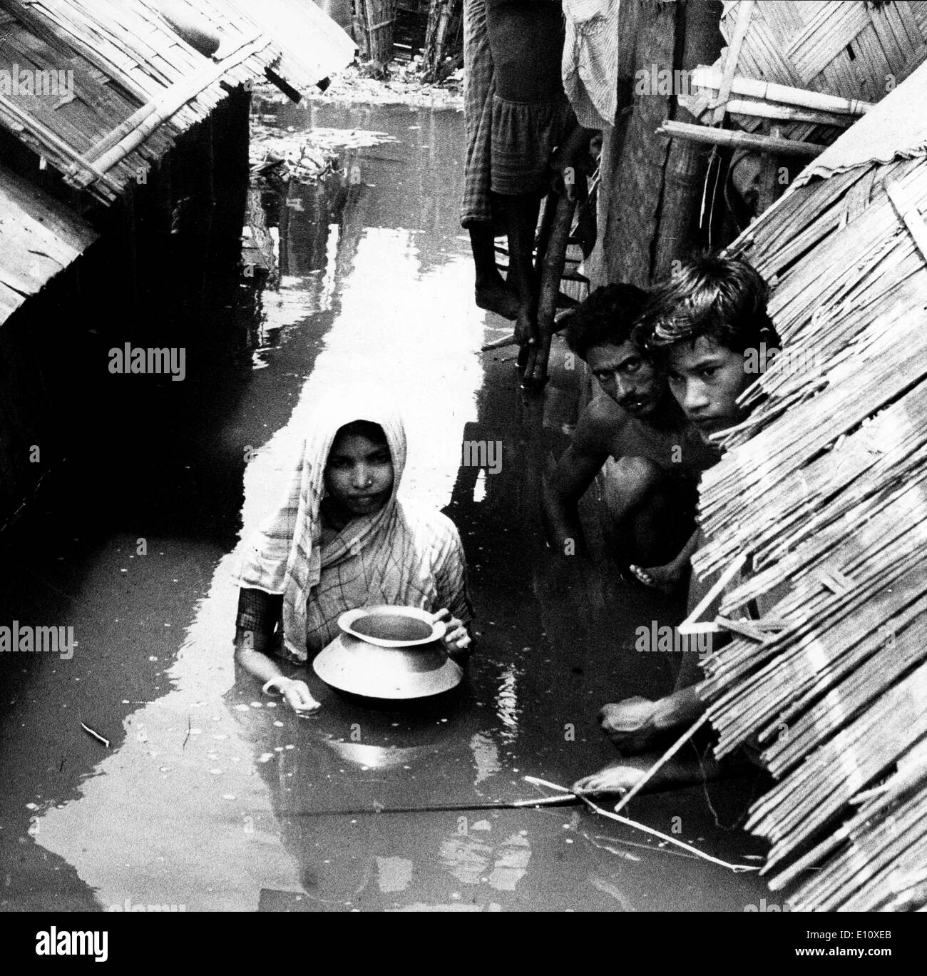 A woman, waist-deep in the 1974 floodwater, Bangladesh - Stock Image