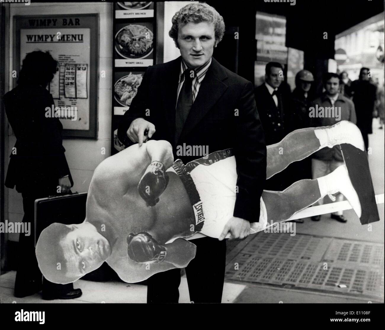 Nov. 05, 1974 - Reception for Jimmy Ellis and Joe Bugner.: Jimmy Ellis of America, former holder of the world heavyweight boxing title, and Joe Bugner, European title holder, who fight at Wembley next Tuesday, today attened a reception at the Sportman's Club in Tottenham Court Road, London. Photo shows Joe Bugner, who hopes that one day he'll carry off the world title, seen holding a life-size picture of world champion Muhammad Ali, outside the Sportmans Club today. - Stock Image