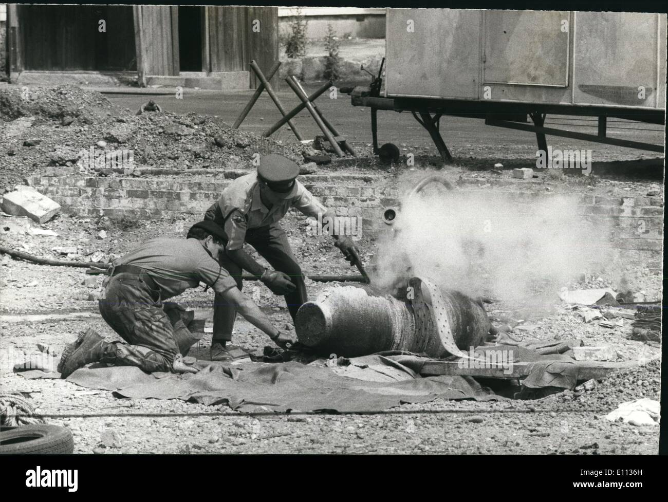 Jul. 07, 1975 - Wartime bomb discovered in Bexleyheath - Kent: Many homes were evacuated in Bexleyheath today as Army bomb disposal experts worked to defuse a 1100 lb. war time bomb discovered in a council yard. Photo Shows Bomb disposal officers work on the bomb whilst they inject into it stream to force the explosive out. - Stock Image