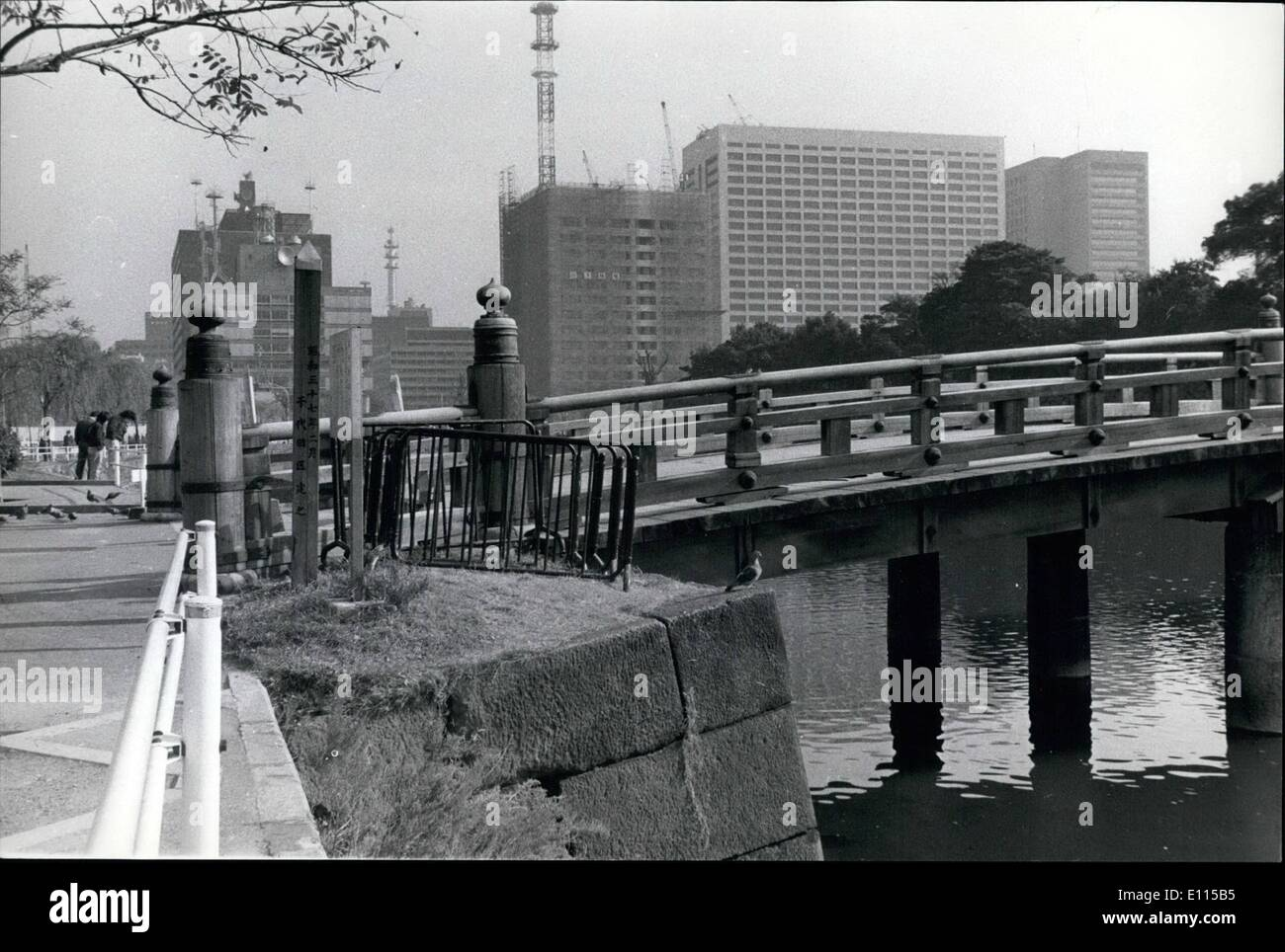 Dec. 12, 1975 - A little of old Edo (Tokyo) remains: The old wooden bridge across the Imperial Palace moat to the Kikyo Mon (Bellflower Gate), built when the city was called Edo, remains solid and dignified in the concrete jungle of modern high rise commercial buildings, that now surround the palace, the residence of the Emperor and Empress of Japan. - Stock Image