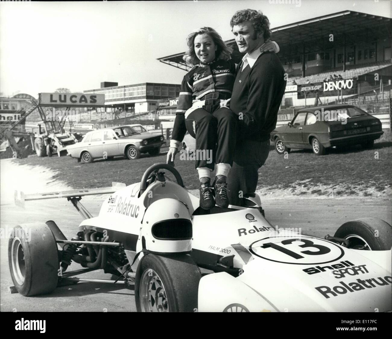 Mar. 03, 1976 - Anne Moore and Joe Bugner practice at Brands Hatch: Joe Bugner was among many Olympic and International sports stars who were today at Brands Hatch practising for next weeks race in aid of the sportsmans charity Starks. Champion Show Jumper Anne Moore who was turned her hand to professional motor racing and will be driving a single seater Elden Ford 2000 in about 30 races this season, was there to give a few words of advice to Joe. Photo shows Anne Moore is helped into her car by Joe Bugner. - Stock Image
