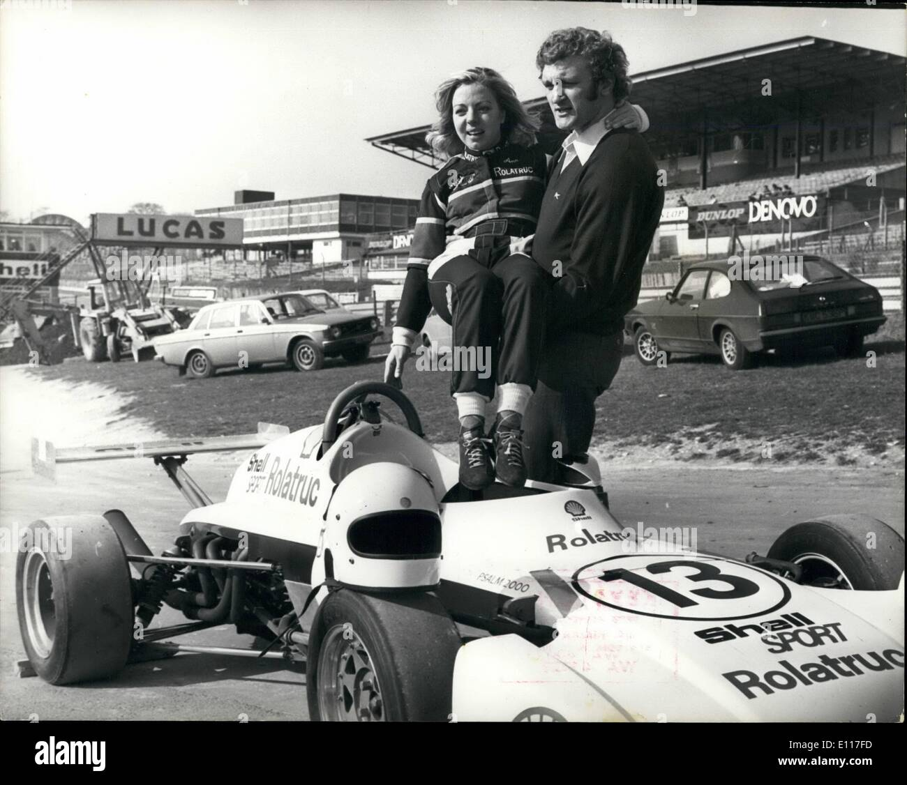 Mar. 03, 1976 - Anne Moore and Joe Bugner practice at Brands Hatch: Joe Bugner was among many Olympic and International sports stars who were today to Brands Hatch practicing for next weeks race in aid of the sportsmans charity Starks. Champion Show Jumper Anne Moore who was turned her hand to professional motor racing and will be driving a single seater Elden Ford 2000 in about 30 races this season, was there to give a few words of advice to Joe. Photo shows Anne Moore is helped into her car by Joe Bugner. - Stock Image