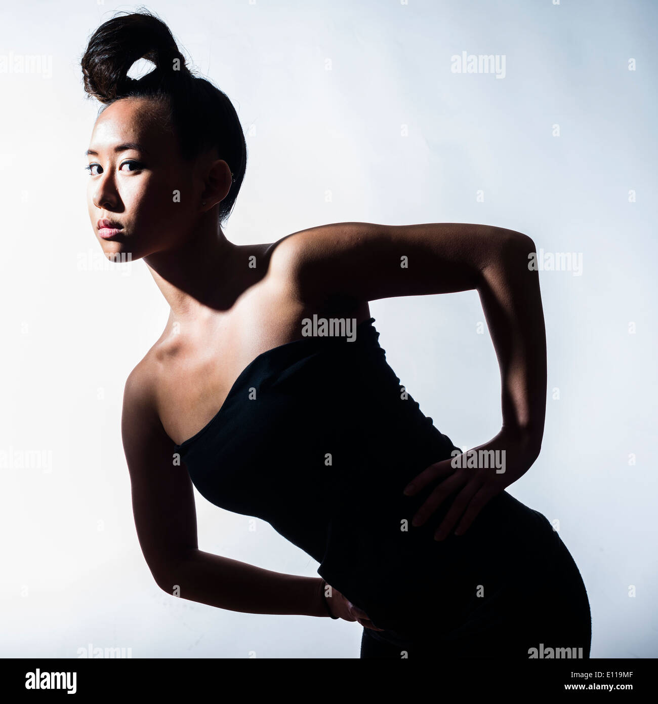 A young slim asian chinese woman girl with her hair tied tightly on her head hands on hips - Stock Image