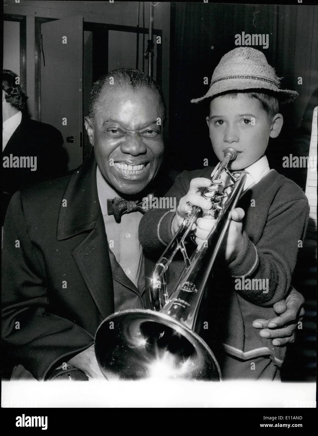Oct. 10, 1976 - Louis Armstrong Arrives, Greeted by A Young Fan. Louis Satchmo Armstrong arrived at London Airport yesterday, and waiting to give him a welcome was one of his biggest fans, 9 years old Enrico Tomasso, who had made the journey from Yorkshire with his father, Mr. Ernie Tomasso, a clarinet player. Enrico had with him the trumpet he's been playing for only three years as Louis listened, Enrico serenaded him with Sleepy Time Down South . Photo Shows: Louis Satchmo Armstrong listens as 9 year old fan Enrico Tomasso serenades him at London Airport yesterday. - Stock Image