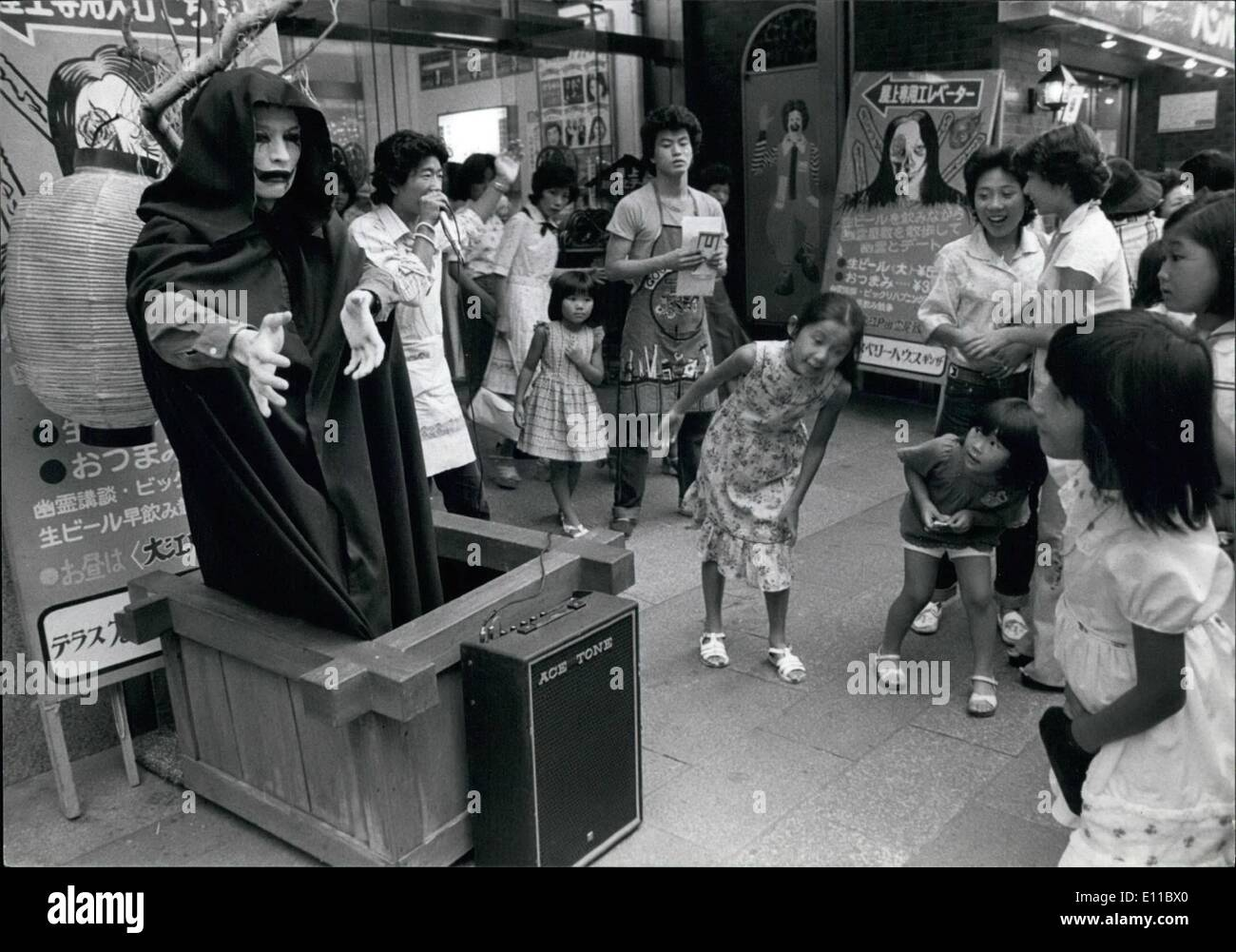 Aug. 08, 1976 - Eerie figures keep Japanese coll in summer heat.: Eerie figures such as ghost, witches, Frankenstein, or Dracula, appear to make the Japanese shiver, and serves to keep them cool in the torrid summer weather. Television feature ghost plays, and magazines print blood-chilling stories, its all part of an old Japanese custom. Outside a beer hall in Ginza, Tokyothe proprietor has placed a witch-like figure to remind passers-by that a nice cold beer is better than shivering by looking at a witch. Children are scared as the witch moves its hands and head. - Stock Image