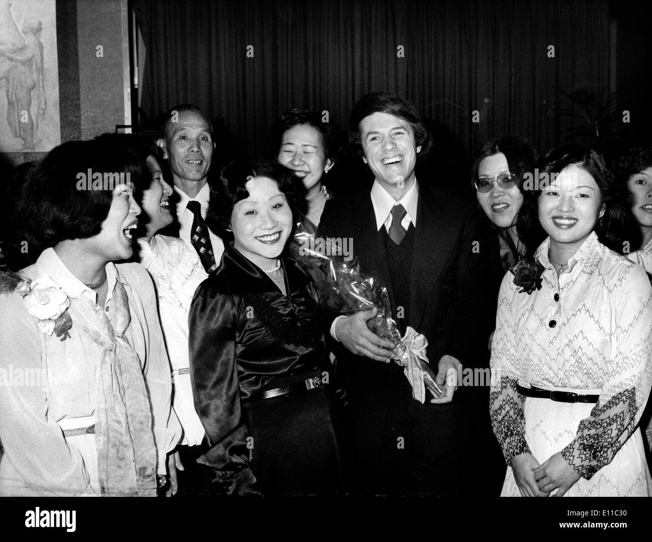 Dec 24, 1976; Paris, France; Winners of a contest from a famous Japanese journal won a trip to Paris to meet their favourite singer, SALVATORE ADAMO, who joyed them to meet the French capital. The picture shows the singer posing with his fans, who gave him some flowers. (Credit Image: KEYSTONE Pictures USA/ZUMAPRESS.com) - Stock Image