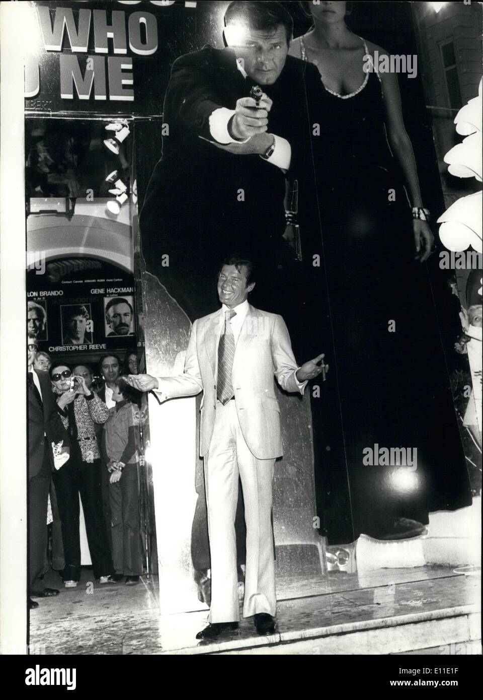 May 23, 1977 - Roger Moore, whose alias is James Bond 007, is currently in Cannes where his latest movie ''The Spy Who Loved Me'' will be exclusively shown as part of the International Film Festival. Picture: Roger Moore in front of a poster of his latest movie in Cannes. - Stock Image
