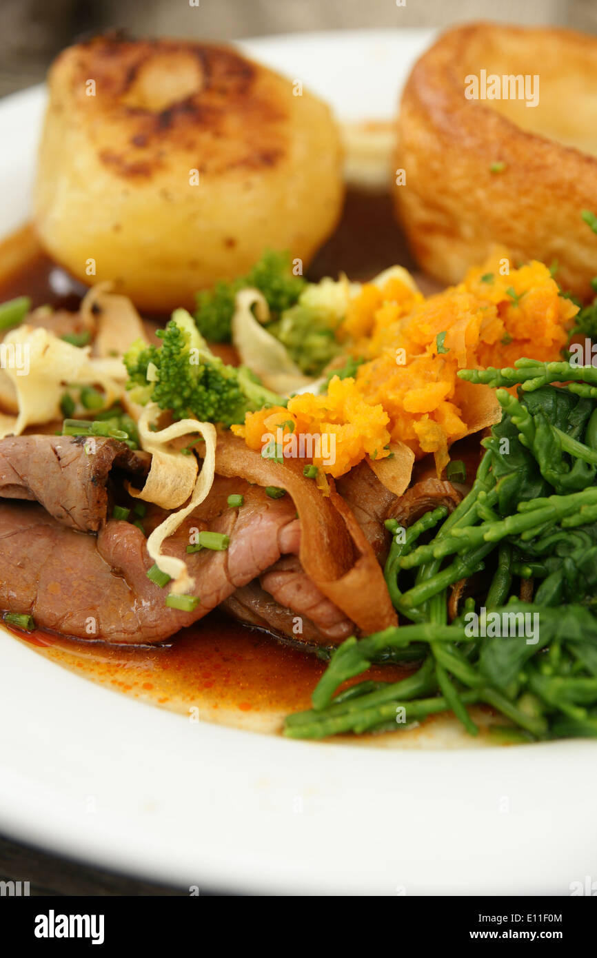 Roast beef dinner with roast potatoes, Yorkshire pudding and vegetables mashed swede and samphire - Stock Image