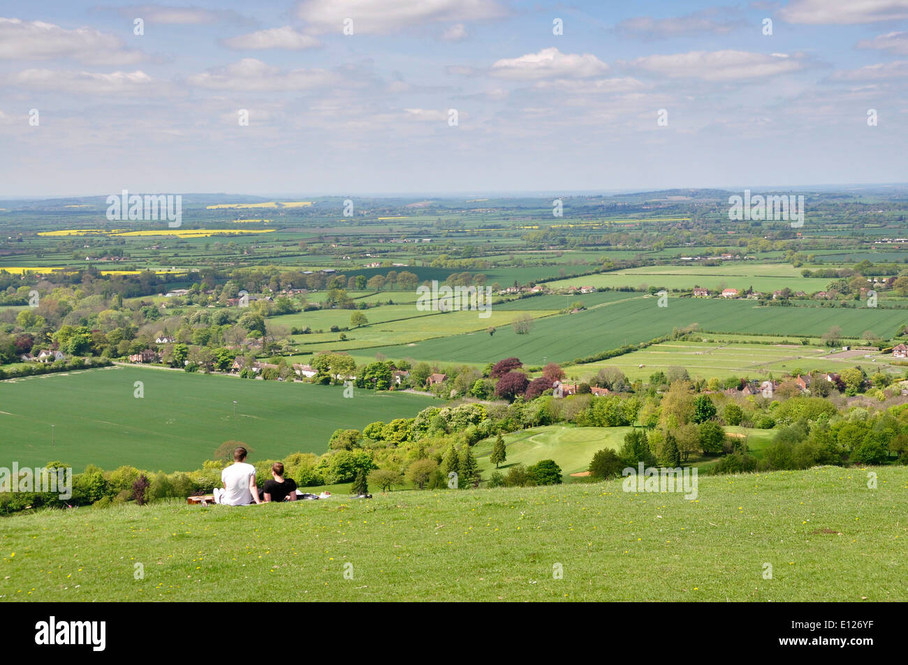 Bucks - Chiltern Hills - Coombe Hill - couple relaxing - enjoying wide view over Aylesbury plain - spring sunlight - blue sky - Stock Image