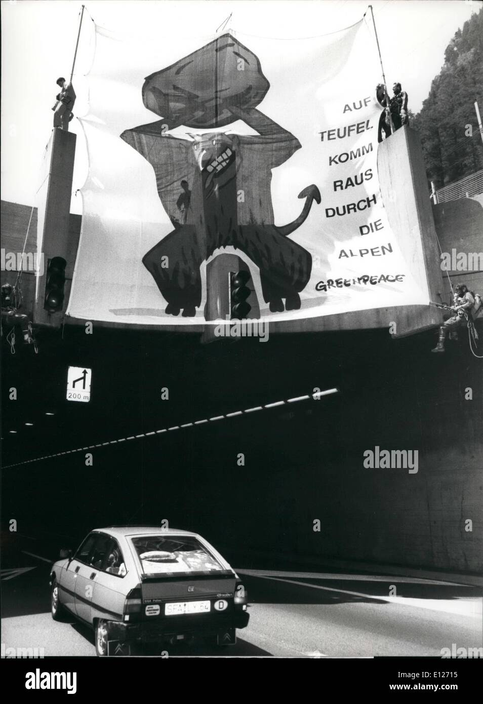 Jul. 07, 1990 - The Devil's Wrath: A huge image of the devil mounted over the entrance to the Gotthard-tunnel met the many drivers travelling South, July 14. Those stuck in the heavy traffic were also given a leaflet by Greenpeace activists that describes in detail the ecological damage caused by individual transport. The Gotthard-route - highly frequented all year through - usually gets jammed during vacation time - Stock Image