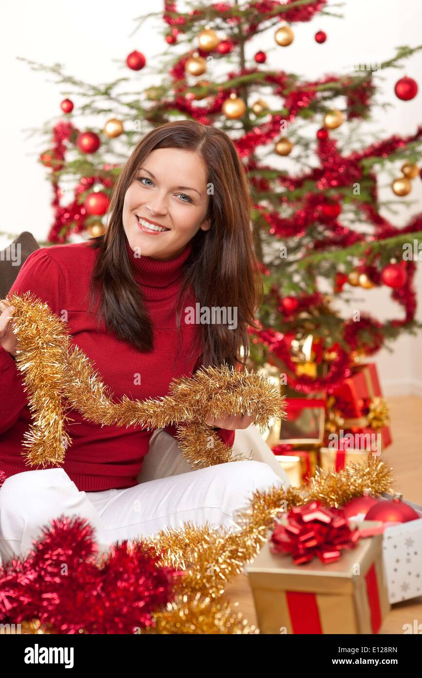 Oct. 06, 2009 - Oct. 6, 2009 - Attractive young woman with Christmas decoration in front of tree - Stock Image