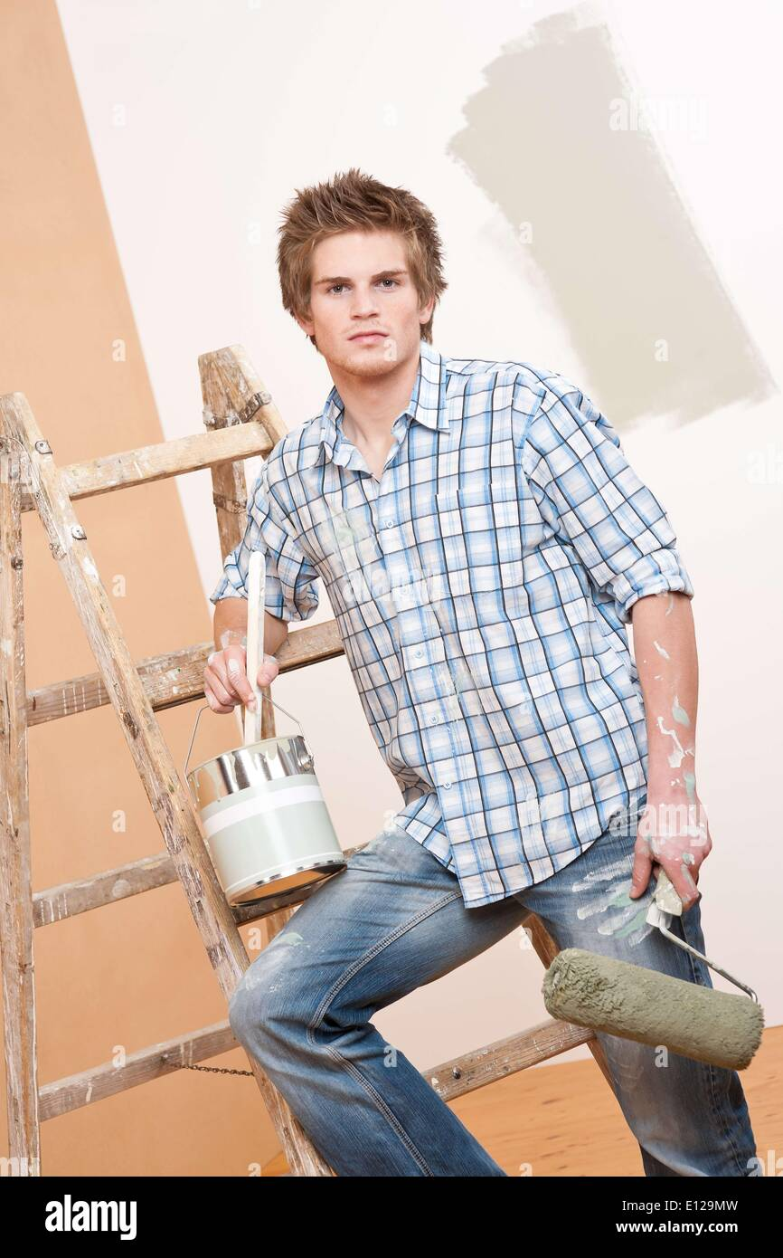Dec. 03, 2009 - Dec. 3, 2009 - Home improvement: Young man with paint roller, paint can and ladder - Stock Image