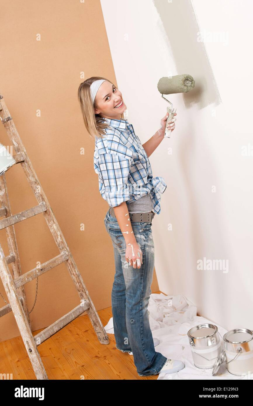 Dec. 03, 2009 - Dec. 3, 2009 - Home improvement: Blond woman painting wall with paint roller - Stock Image