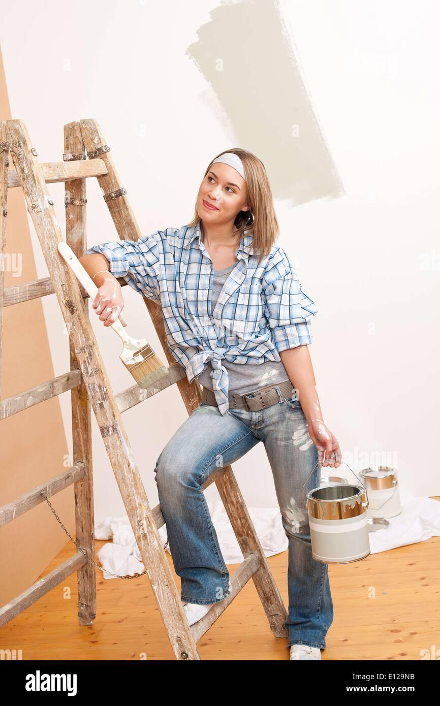 Dec. 03, 2009 - Dec. 3, 2009 - Home improvement: Smiling woman with paint and brush painting wall - Stock Image