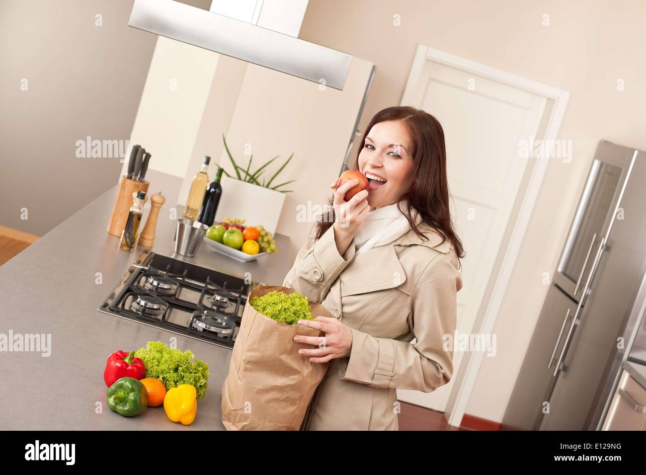 Jan. 23, 2010 - Jan. 23, 2010 - Young woman unpacking shopping bag with grocery in kitchen, biting apple - Stock Image