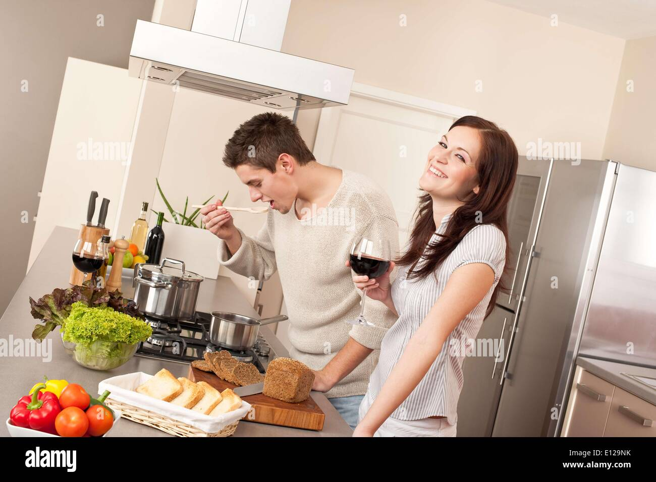 Jan. 23, 2010 - Jan. 23, 2010 - Young couple cooking in kitchen together drinking red wine - Stock Image