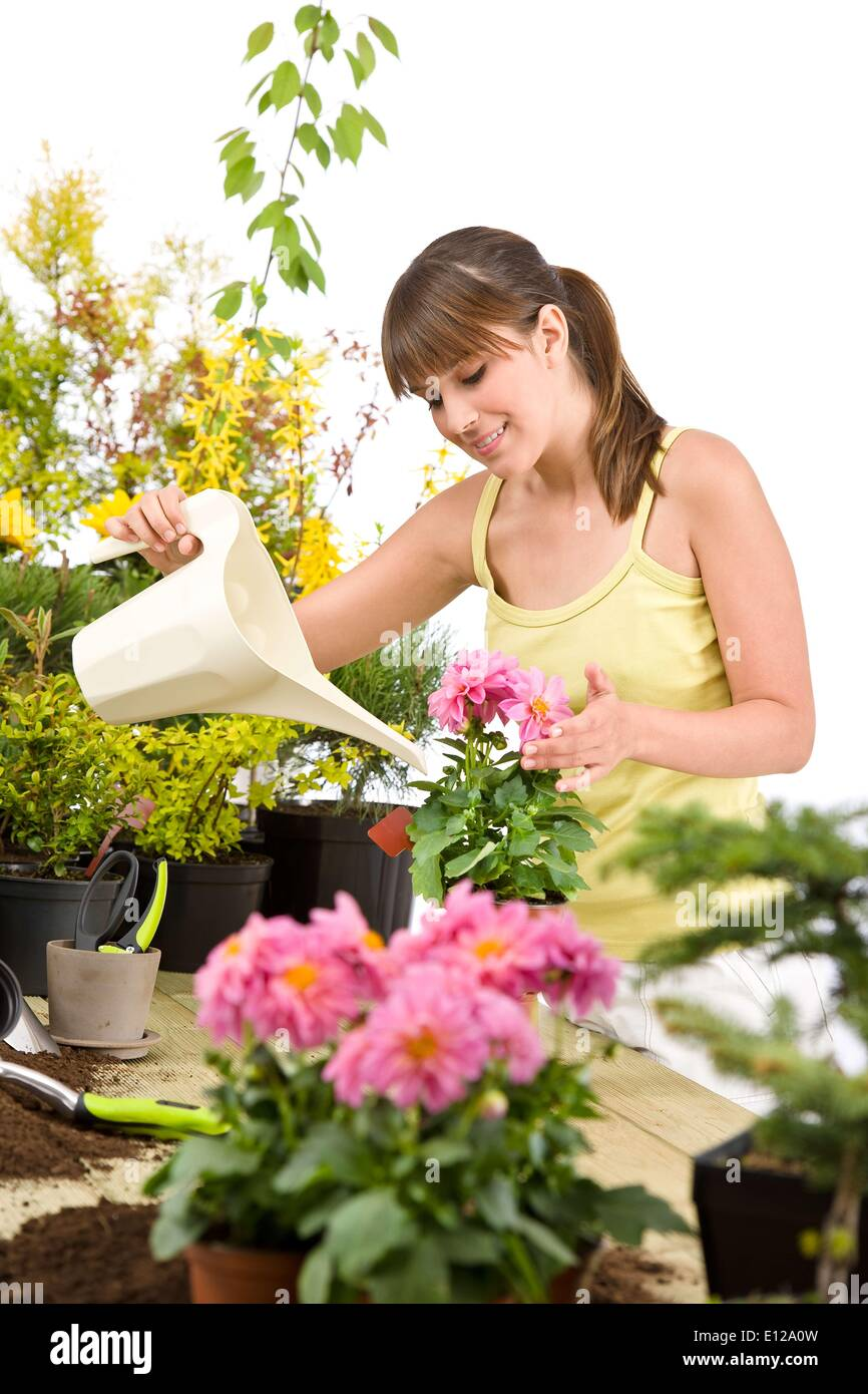 May 01, 2010 - May 1, 2010 - Gardening - woman with watering can and flowers pouring water on white background Ã' - Stock Image