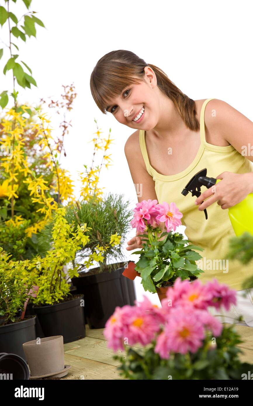 May 01, 2010 - May 1, 2010 - Gardening - smiling woman with flower and sprinkler on white background - Stock Image