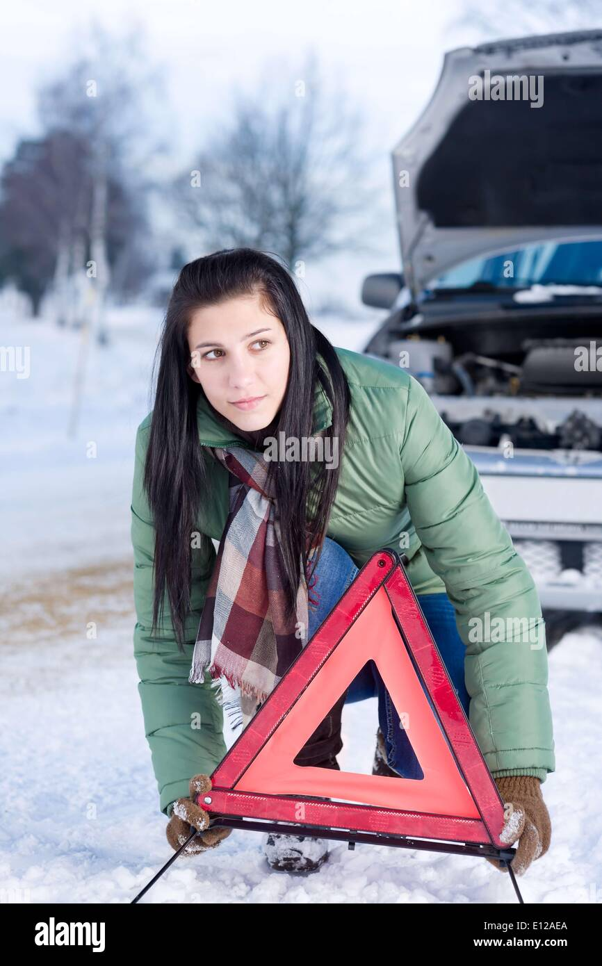 Dec. 02, 2010 - Dec. 2, 2010 - Winter car breakdown - woman placing warning triangle - Stock Image