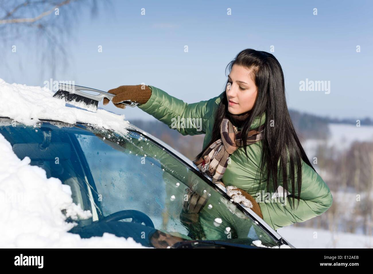 Dec. 02, 2010 - Dec. 2, 2010 - Winter car - woman remove snow from windshield with snow brush - Stock Image