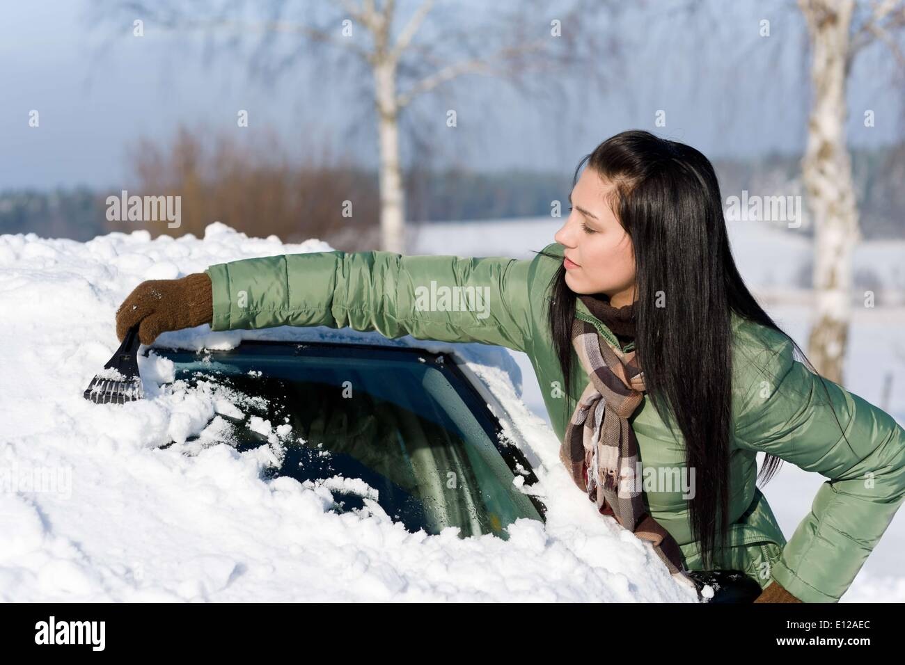 Dec. 02, 2010 - Dec. 2, 2010 - Winter car - woman remove snow from windshield with ice scraper - Stock Image