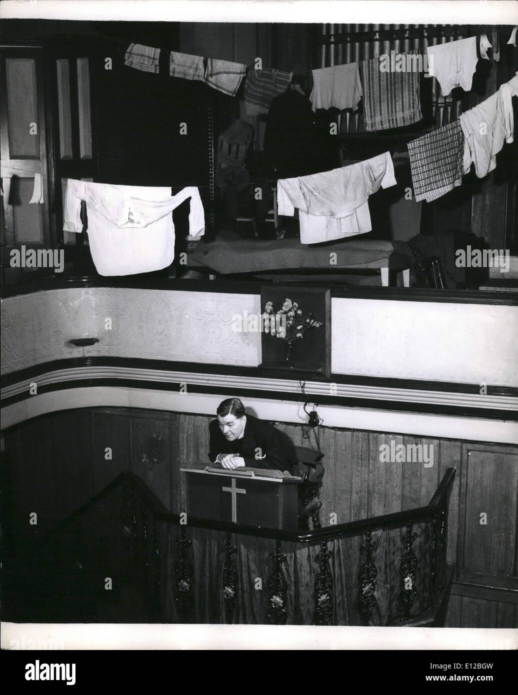 Dec. 09, 2011 - The sermon beneath the washing. The Rev. Bertarm Peake preaches from the pulpit of Golborne Church, Kensington. Before him in the pews are his flock , many of them former prisoners. Above him, not quite hidden, in the gallery is their washing hanging out to dry, and their beds. The pulpit was presented to the church by the brother of a professional Atheist who made this last request to the Rev. Peake when he was dying. - Stock Image