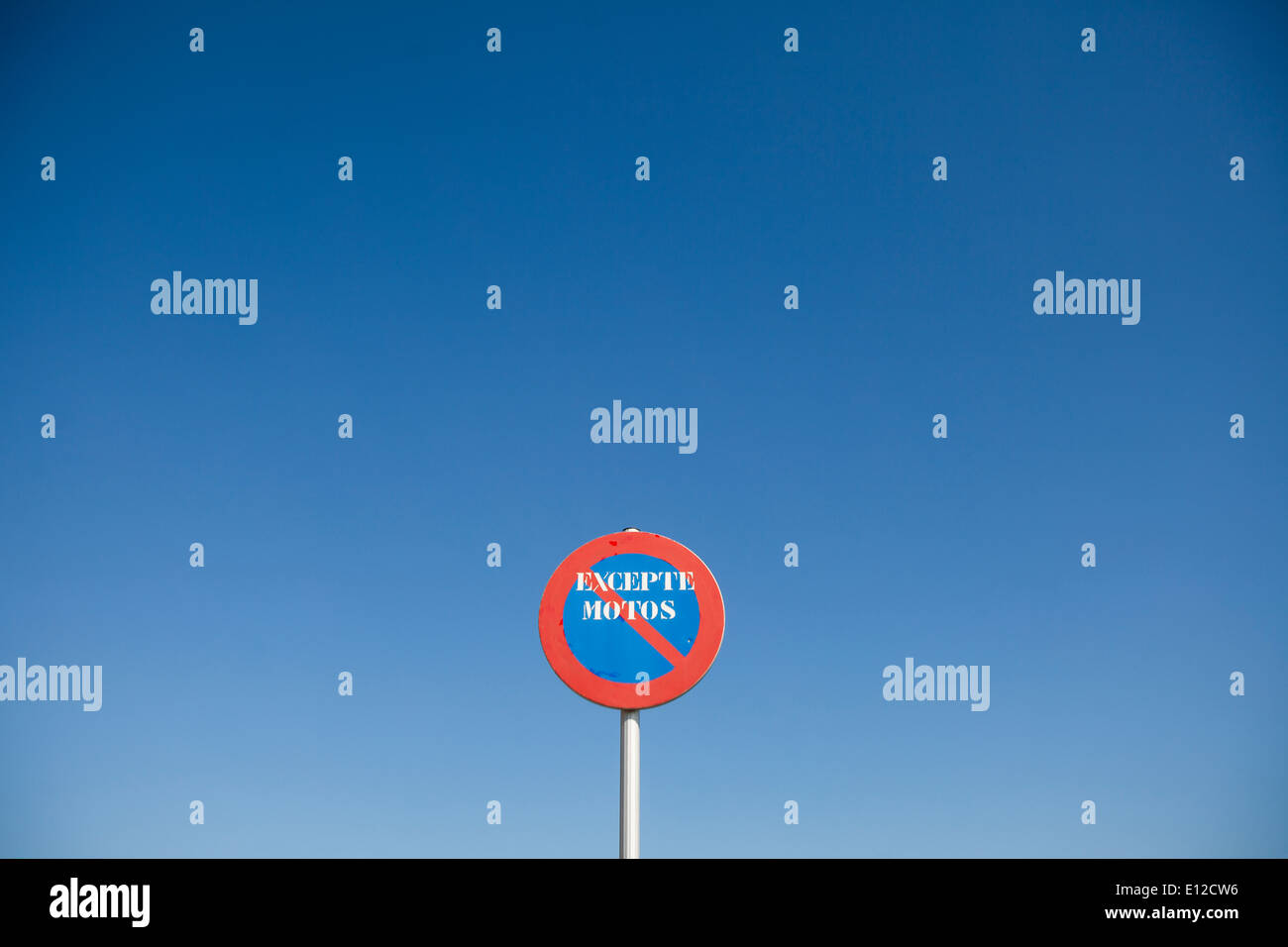 Traffic signal written in Catalan: Except motorbikes - Stock Image