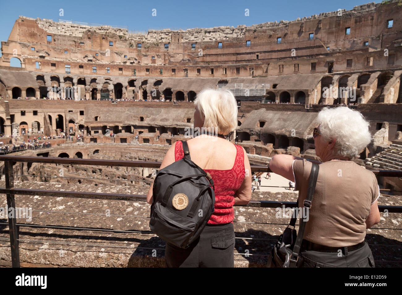 Two elderly people on holiday visiting the Colosseum, Rome interior, aka the Flavian Amphitheatre, Rome Italy Europe - Stock Image