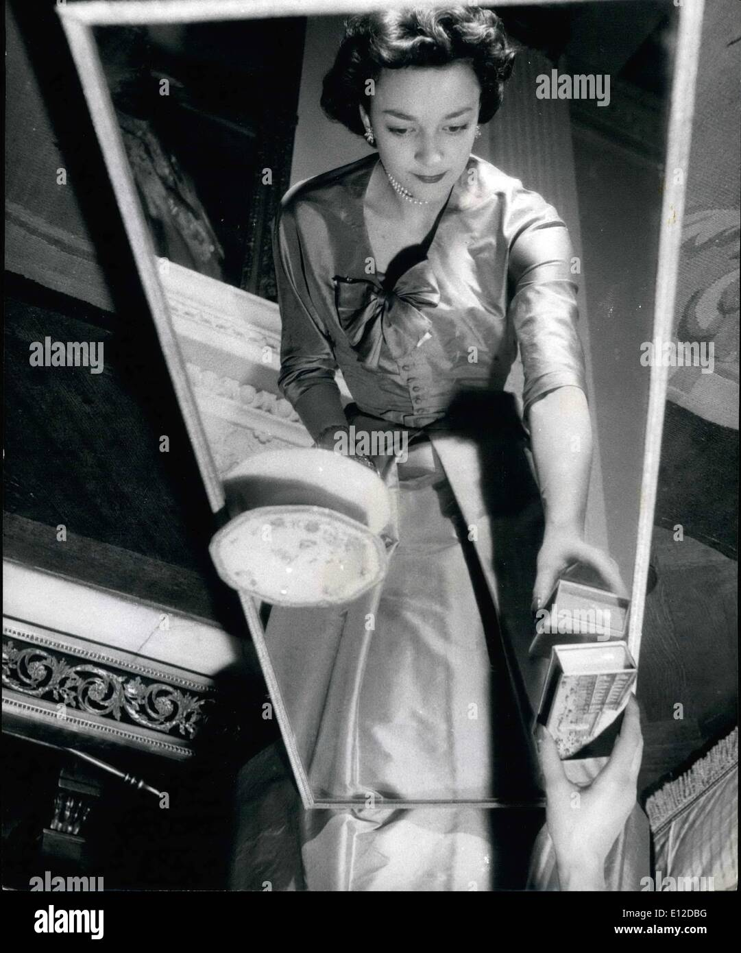 Dec. 19, 2011 - An unusual photograph of Lady Mary Baillie-Hamilton reflected in the mirror top table in the drawing room of her home at Chelsea. She Will Attend The Queen On Coronation Day: Six beautiful girls whose ages range from 17 to 83 have been chosen by the Queen to be her Maids of Honour at the Coronation Service. Queen Victoria set the precedent when she was crowned. Maids of Honour instead of the usual Pages carried her train. The girls are being trained by Mary, Duchess of Devonshire, Mistress of the Robes to the Queen - Stock Image