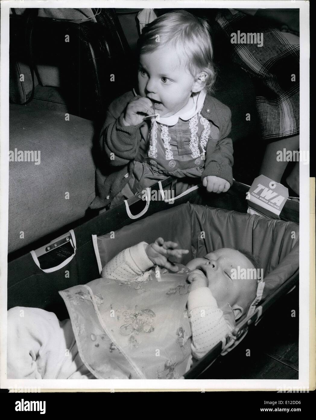 Dec. 19, 2011 - Janet Sue Vaughn, 8 months, moved in on sleeping Keith Nix, 8 months, and yanked his pacifier from his mouth while waiting to board their TWA Jetstream flight to Europe. Janet Sue, of New Castle, Indiana, will be joining her daddy, who is in the Army, in Frankfurt. Keith who hails from Atlanta, Georgia, is headed for Madrid where his dad Airman 2/C W.K. Nix is based. - Stock Image