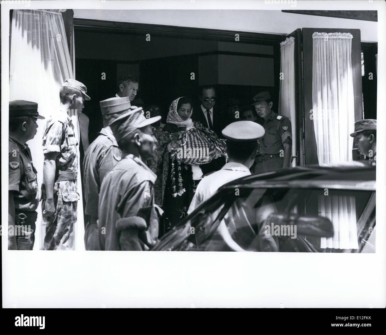 Dec. 26, 2011 - On her way - Mrs Abdul Haris Nasution, wife of Indonesia's Defense Minister, leaves their home in Djakarta in the morning of Oct 7, 1965 carrying the body of her 5-year-old daughter, who was killed during the communist abortive coup of Oct 1. As is Muslim custom, the body is not placed in a casket, but is wrapped in cloth and buried. Mrs Nasution carried the girl on her lap in the car to the cemetery. - Stock Image